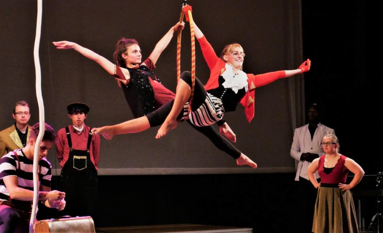 Two performers make star poses, crossing their bodies through a hoop which is suspended from the ceiling on stage, around them five other performers stand and watch, they are all wearing costumes with smart blazer jackets and in the theme of red black and mustard colours