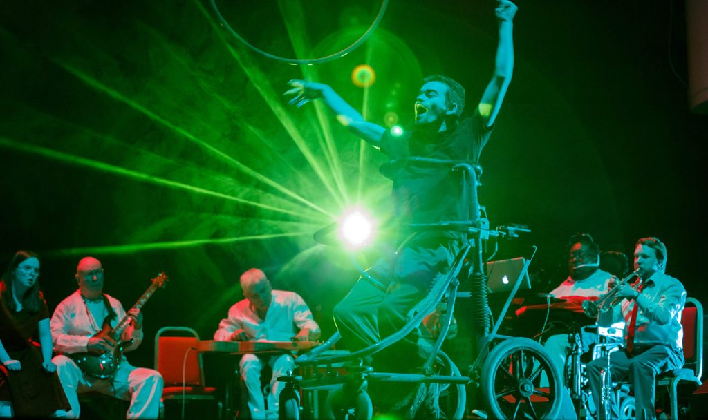A performer dances in the centre using a walker with wheels, behind him Paraorchestra plays their instruments and they are lit from behind by a green light